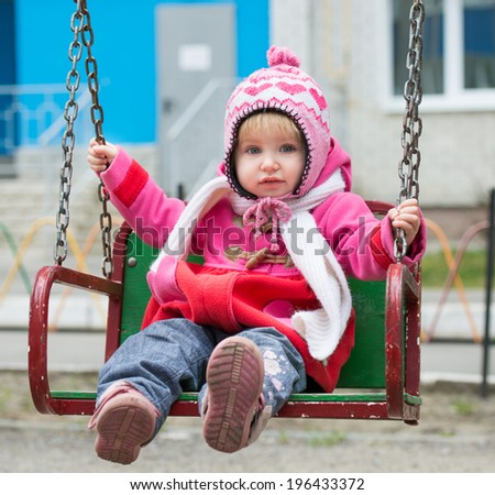 Little girl on the playground ride on a swing - stock photo