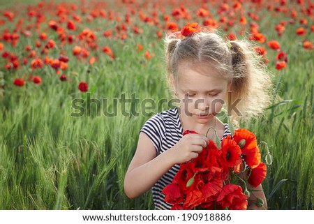 Little girl on the poppy meadow with posy examining flowers - stock photo