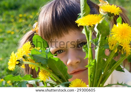 Little girl on the spring meadow peeps out through the bunch of dandelions - stock photo