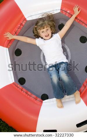 Little girl on trampoline - stock photo