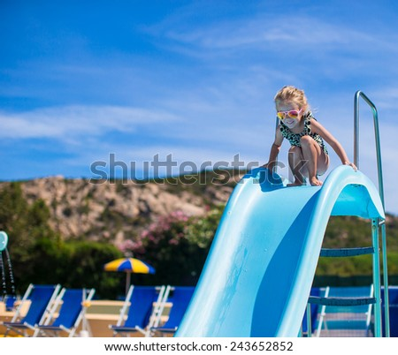 Little girl on water slide at aquapark on summer holiday - stock photo