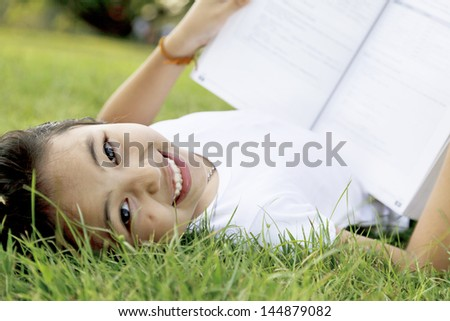 Little girl opened the book in the park