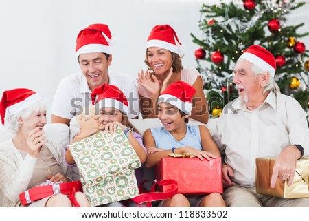 Little girl opening christmas present on couch with family - stock photo