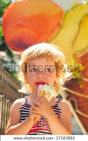 little girl outdoors eating huge ice cream cone - stock photo