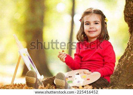 Little girl paint in a park - stock photo