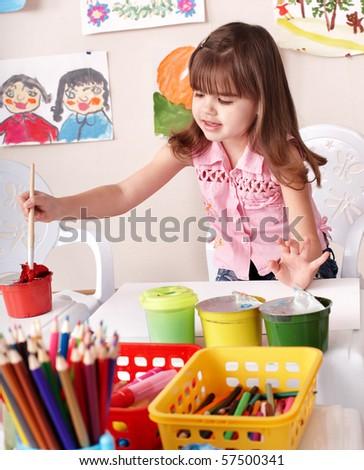 Little girl paint picture in preschool. - stock photo