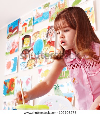 Little girl paint picture in preschool. Child care. - stock photo