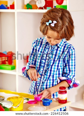 Little girl painting at easel in school. Education. - stock photo