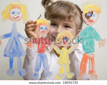 Little girl painting family on glass - stock photo