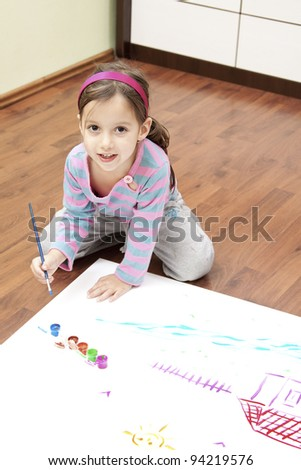 Little girl painting in her room - stock photo