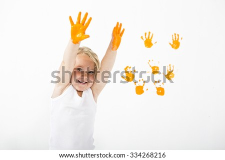 Little girl painting white wall with orange color and handprints - stock photo