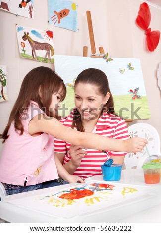 Little girl painting with mother at home. - stock photo
