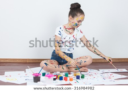 little girl painting with paintbrush and colorful paints. Child painting. - stock photo