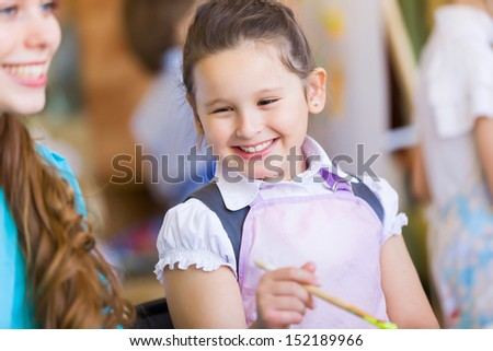 Little girl painting with teacher at kindergarten