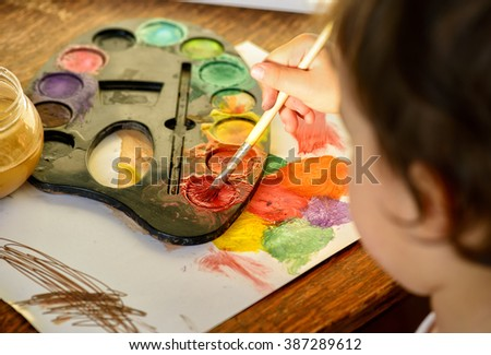 Little girl painting with water color - top view - stock photo