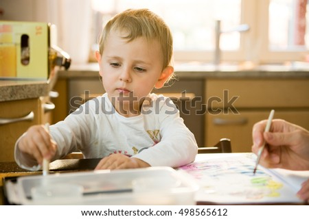 Little girl painting with watercolor at home in the kitchen