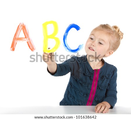 Little girl paints ABC's or letters on window, isolated on white