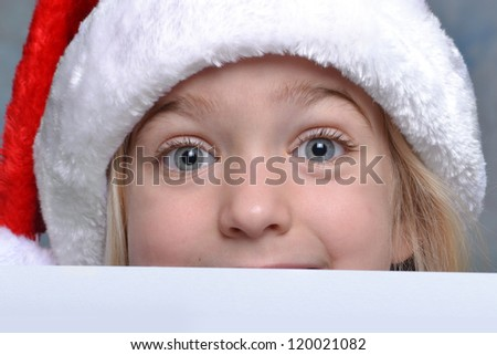 little girl peeking over a christmas list - stock photo