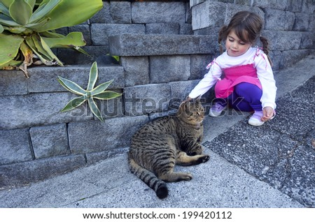 Little girl petting a cat outdoor.Concept photo of pet , child, childhood, realtionship, care. - stock photo