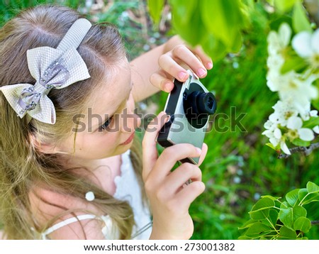 Little girl photographs blossoming tree at spring. Romantic style. - stock photo