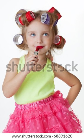 Little girl play big applying lipstick and wearing hair rollers - stock photo