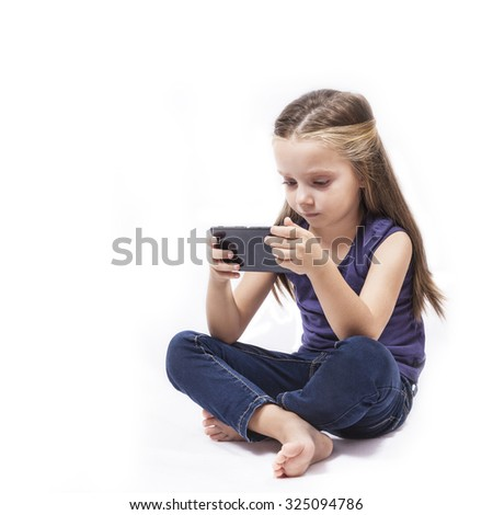 Little girl play with her smartphone - stock photo