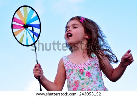 Little girl play with pinwheel  toy windmill outdoors. concept photo seasonal and weather - stock photo