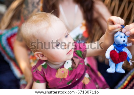 Little girl playing a toy in sunlight. Ecology concept. Happy baby girl in a wreath on meadow. Copyspace.