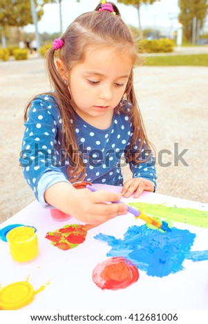 little girl playing and painting in a park