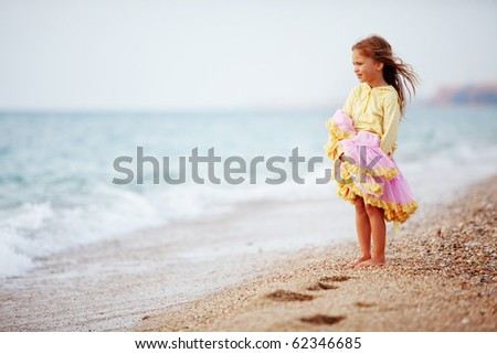 Little girl playing at the autumn beach - stock photo