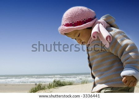 little girl playing at the beach - stock photo