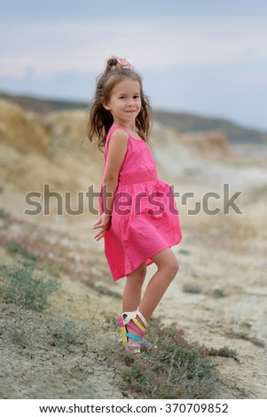 Little girl playing at the summer beach in a pink dress