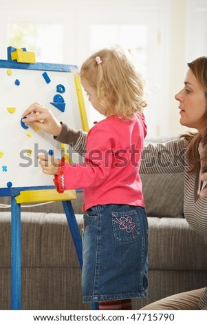 Little girl playing board game with mum in living room. - stock photo