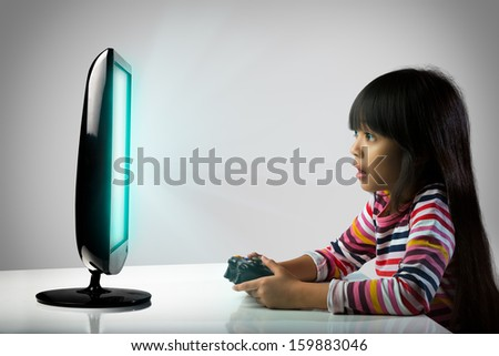 Little girl playing computer games, Kids addicted to the game concept - stock photo