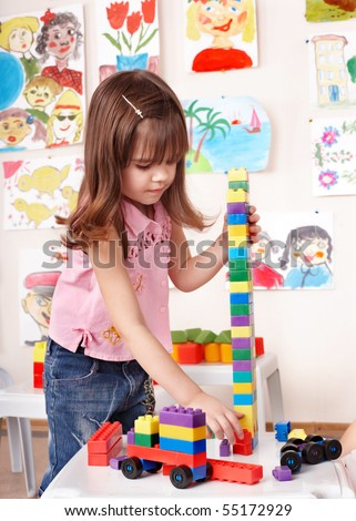 Little girl playing  construction set in play room. - stock photo