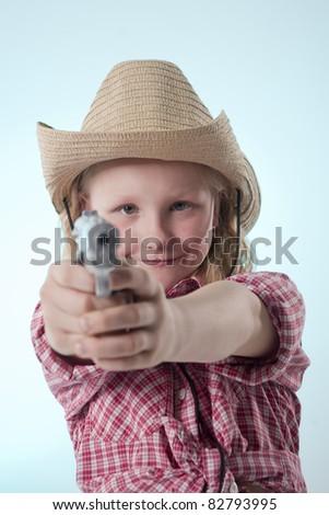 Little girl playing cowboys aiming a gun - stock photo