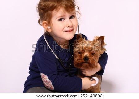 Little girl playing doctor with a dog - stock photo
