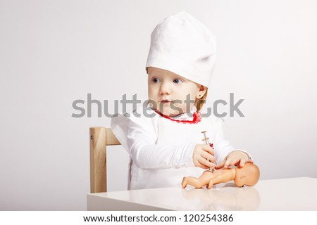 little girl playing doctor with a doll - stock photo