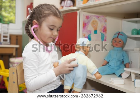 Little girl playing doctor with a doll in the nursery