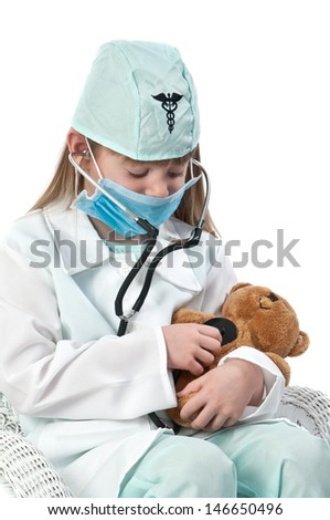 Little girl playing doctor with teddy bear - stock photo