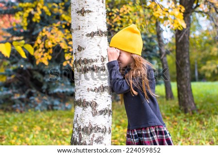 Little girl playing hide and seek in autumn forest outdoors - stock photo