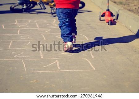 little girl playing hopscotch on asphalt outside - stock photo