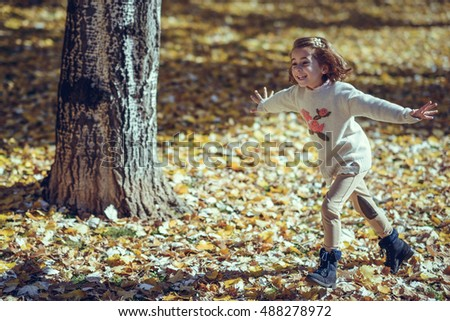 Little girl playing in a city park in autumn, wearing pants and jersey with a hairpin in hair