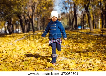 Little girl playing in autumn park - stock photo