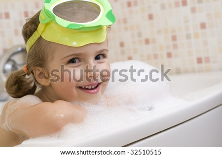 Little girl playing in foam - stock photo
