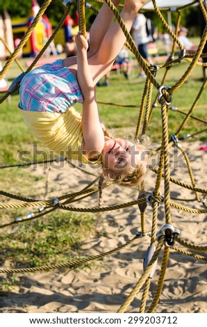little girl playing in ropes in playground - stock photo