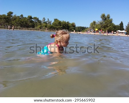 little girl playing in sea - stock photo