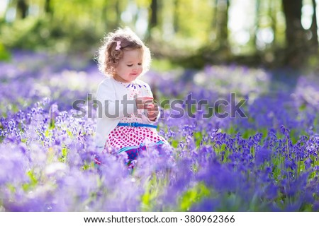 Little girl playing in sunny blooming garden. Baby on Easter egg hunt in blue bell flower meadow. Toddler child picking bluebell flowers. Kids play outdoors. Spring fun for family with children. - stock photo