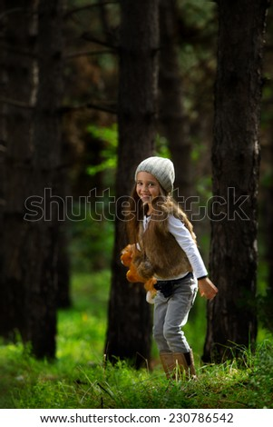 Little girl playing in the forest - stock photo