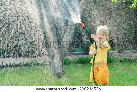 Little girl playing in the garden pouring all the water from a garden hose. MANY OTHER PHOTOS FROM THIS SERIES IN MY PORTFOLIO. - stock photo